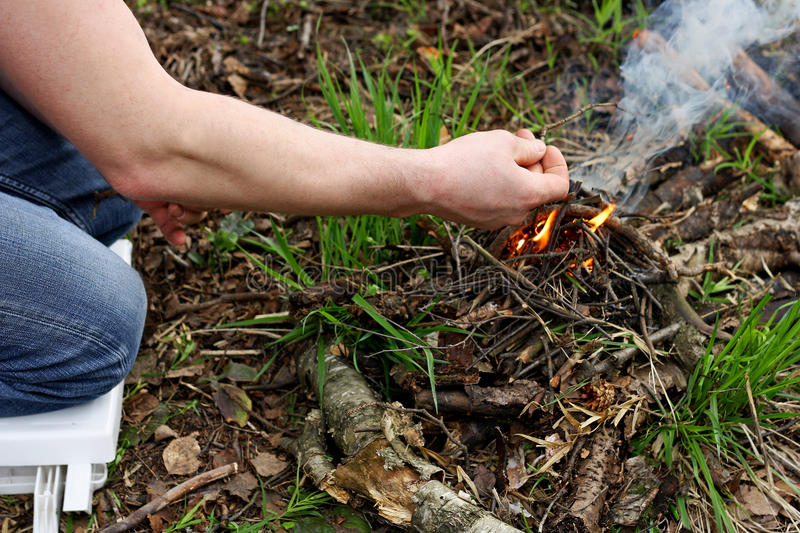 Man kindle a fire in the forest. The man in the woods. The man sitting on his knees in the forest among the dry, withered leaves. People kindle fire stock photo