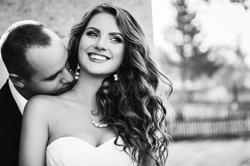 Man kisses soft neck of delightful woman with long curls royalty free stock photo