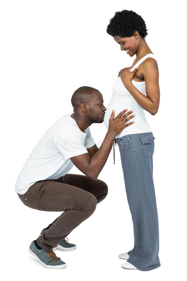 Man kissing the belly of pregnant woman stock photo
