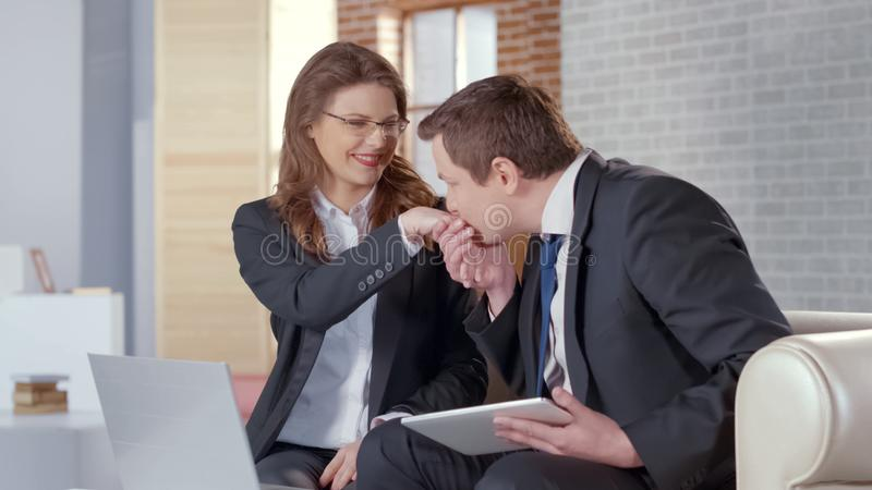 Man kissing businesswoman hand, partners celebrating successful agreement stock photos