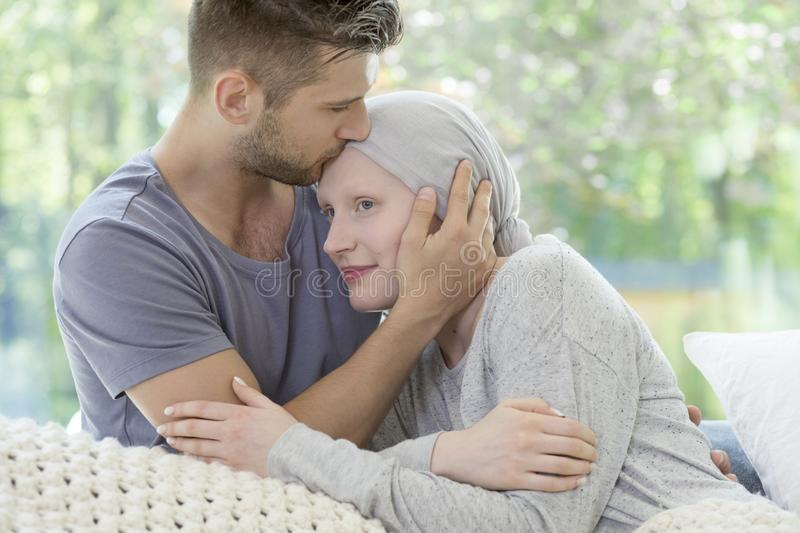 Man kissing his sick girlfriend on the forehead. Support during. Cancer treatment concept stock photos