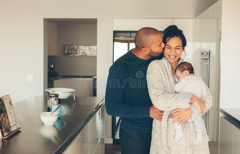 Lovely young family of three in kitchen royalty free stock images