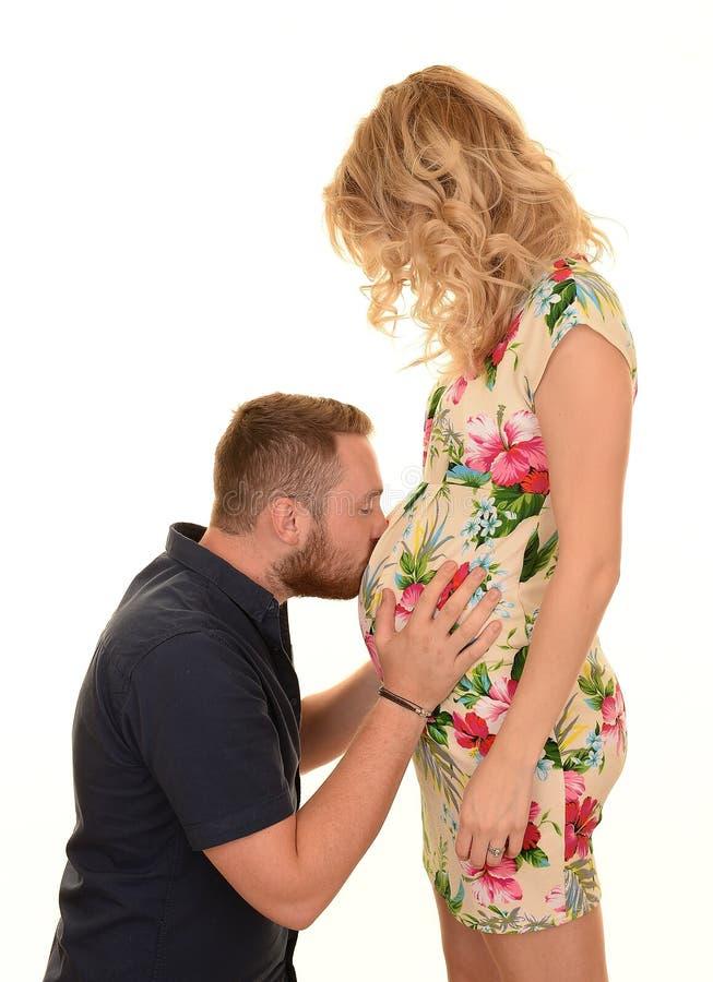 Man kissing pregnant woman's baby bump. Man kissing the baby bump on a pregnant woman stock photos