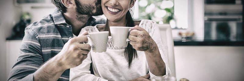 Man kissing on woman cheeks while having breakfast stock photos