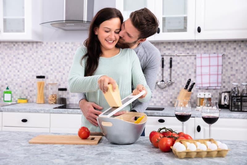 Man Kissing Woman While Making Delicious Fresh Food. Happy Man Kissing His Wife While Making Delicious Fresh Food In Kitchen royalty free stock image