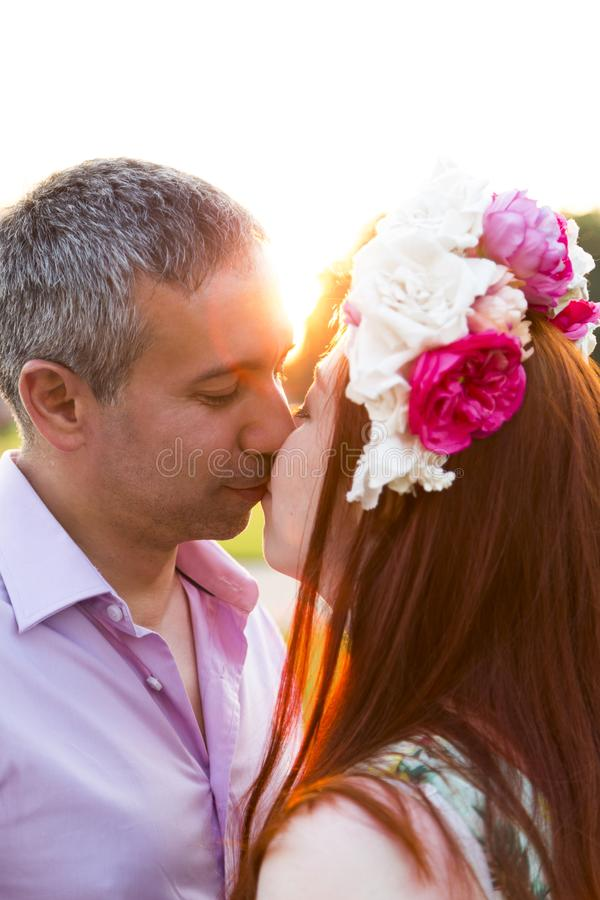 Man kissing woman wearing flower wreath in park stock photo
