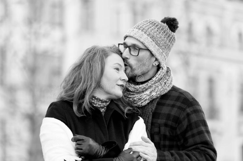 Man in glasses kissing woman. Guy embracing girl and kiss. Urban people love outside dates. Family. Man kissing women in forehead. Man in glasses kissing woman royalty free stock image