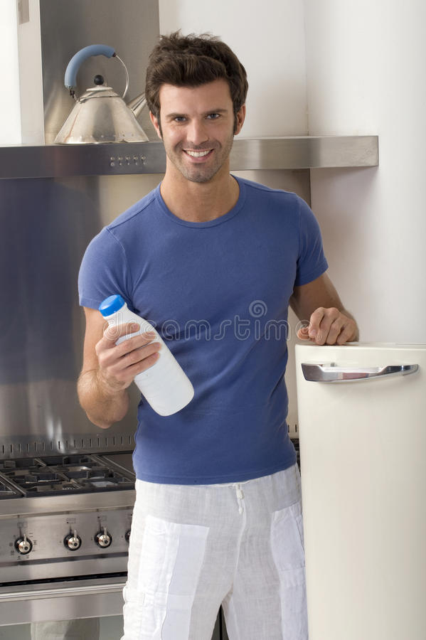 Download Man In The Kitchen With A Bottle Of Milk Stock Photo - Image: 17990124
