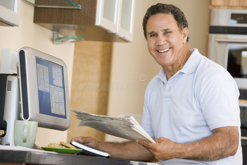 Man in kitchen with computer and newspaper smiling royalty free stock photo