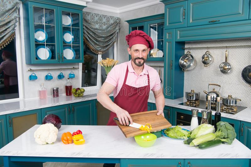 Man at kitchen cooking vegetable salad with paprika and mushrooms. Handsome chef cut orange pepper. Vegetables for healthy life royalty free stock photos