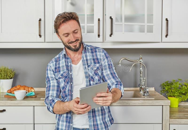 Man in kitchen with digital tablet stock image
