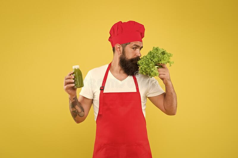 Man on kitchen. healthy eating and dieting concept. cook hold fresh blended salad smoothie bottle. organic eco vegan. Products. bearded man chef in apron and royalty free stock photography