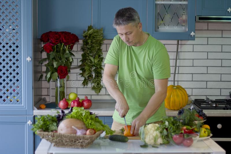 A man in the kitchen prepares vegetarian dishes.Cook standing at the kitchen table. Vegetables , ready for cooking stock images