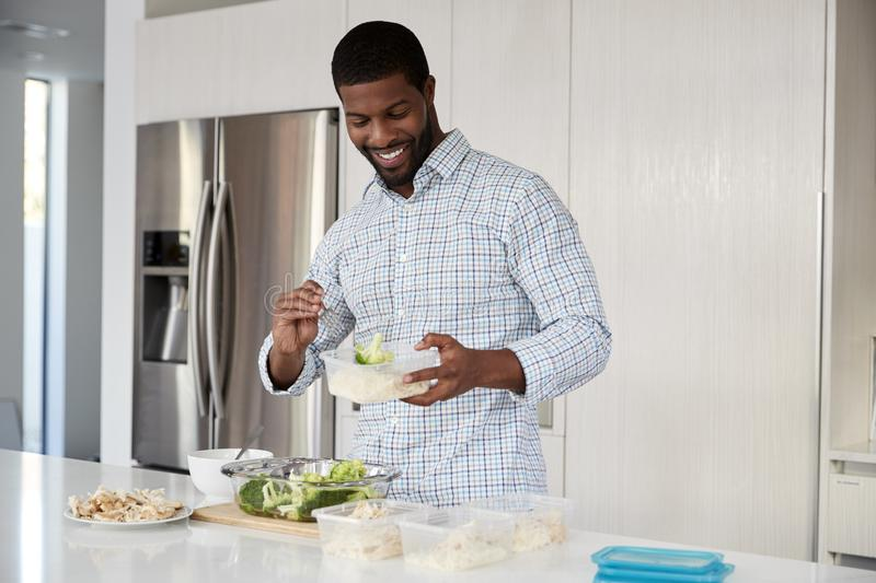 Man In Kitchen Preparing High Protein Meal And Putting Portions Into Plastic Containers stock photo