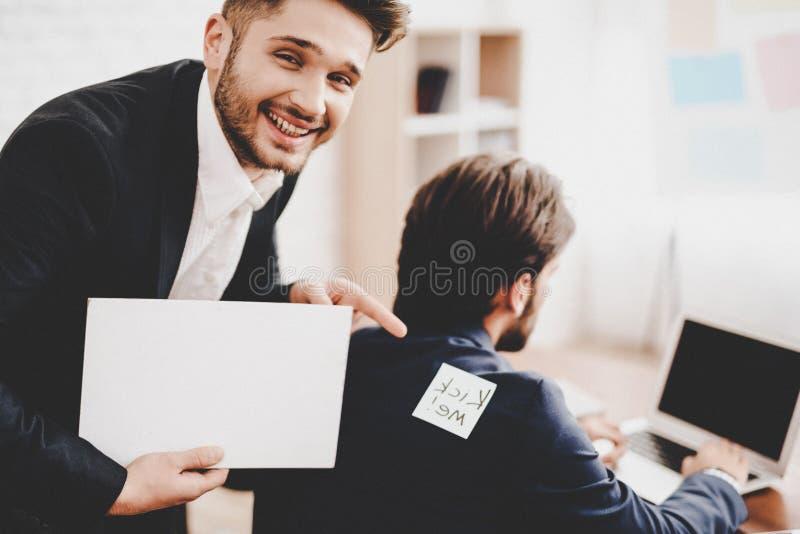 Man klistrad klistermärke på baksida av kollegan i regeringsställning royaltyfri foto