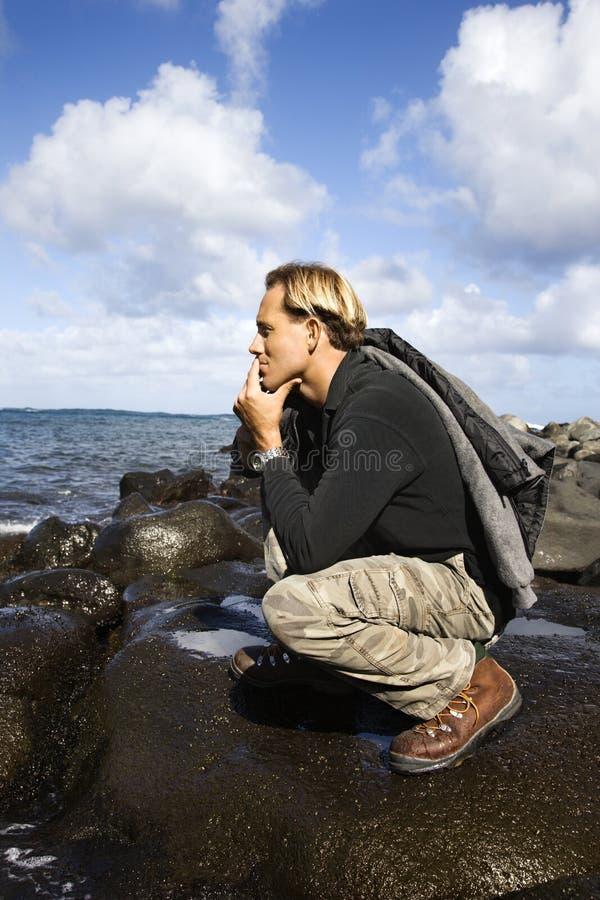 Man kneeling by the coast of Maui, Hawaii. royalty free stock image