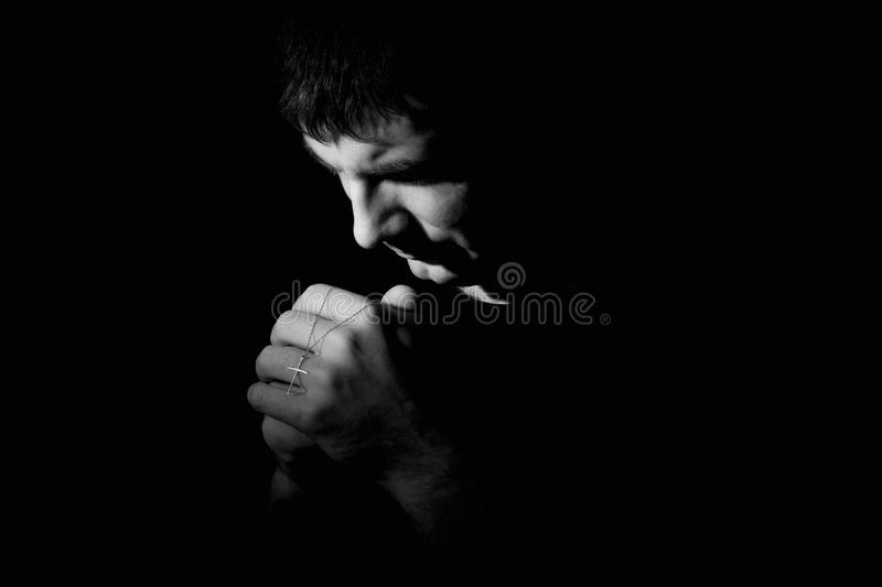 Man kneeling down praying to God. A black and white image of a man kneeling down praying to God stock images