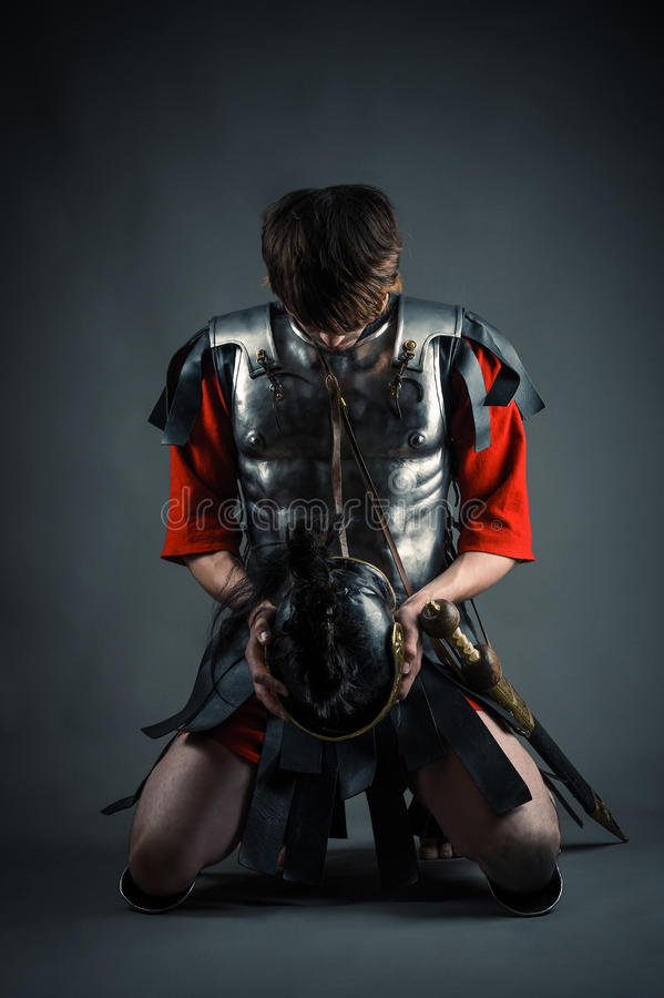Man kneeling with a helmet in hands stock photo