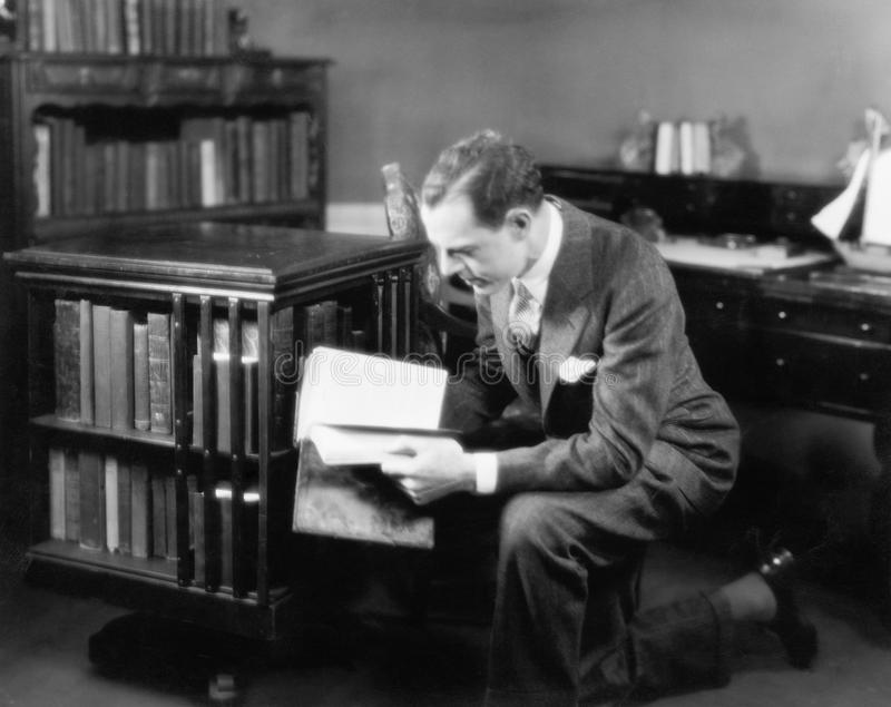 Man kneeling in his home library browsing a book. (All persons depicted are no longer living and no estate exists. Supplier grants that there will be no model royalty free stock image
