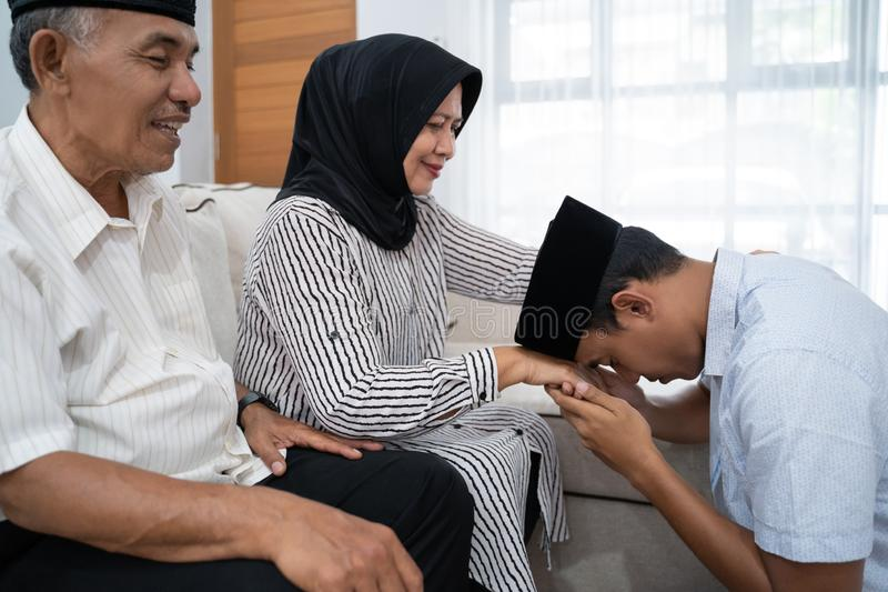 Man kneeling and kiss his parent`s hand asking for forgivness royalty free stock photos