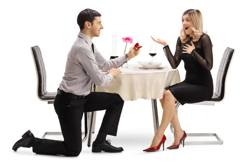Man kneeling and proposing with a ring to a woman at a dinner table. Full length shot of a men kneeling and proposing with a ring to a women at a dinner table stock photos