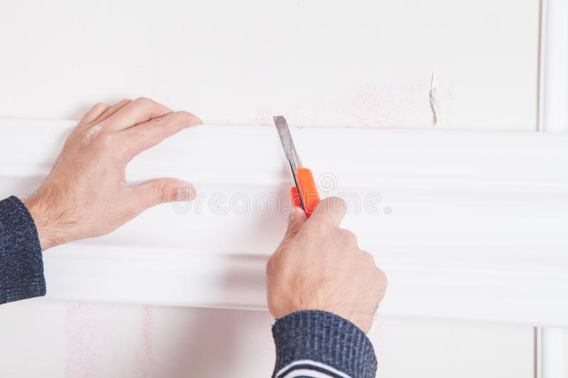 Man with knife cutting ceiling skirting. stock photography