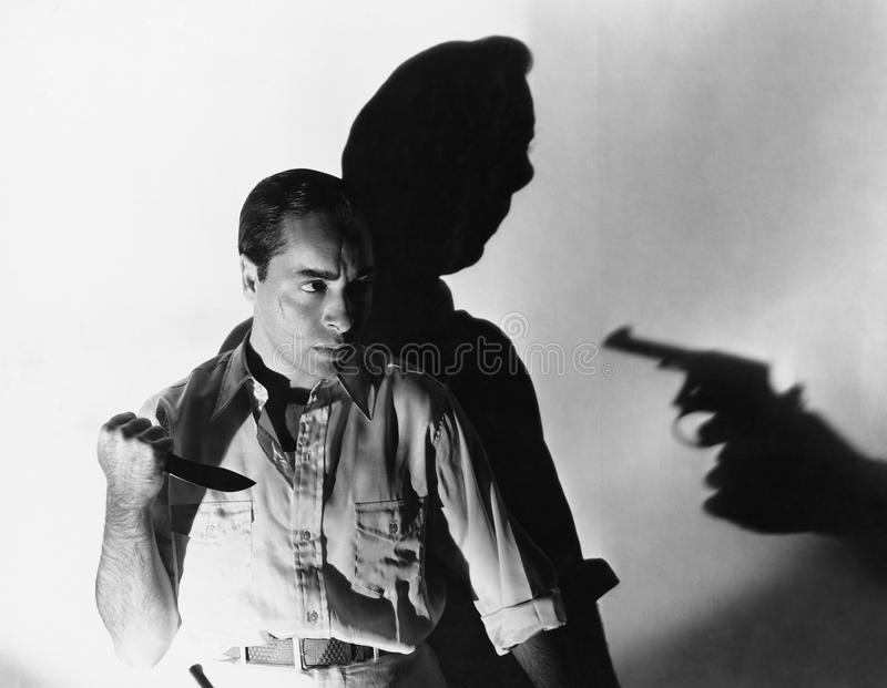 Man with knife at gunpoint stock image