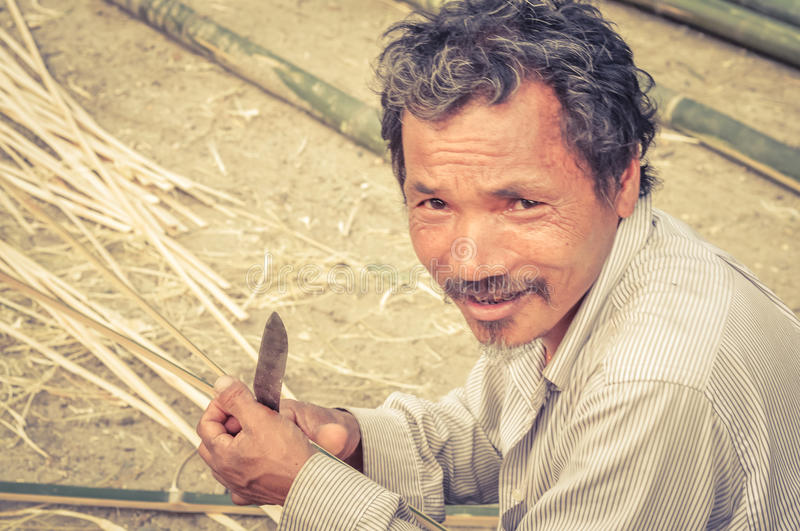 Man with knife in Nepal. Damak, Nepal - circa May 2012: Old man dressed in white clothes holds knife at Nepali refugee camp in Damak, Nepal. Documentary stock photography