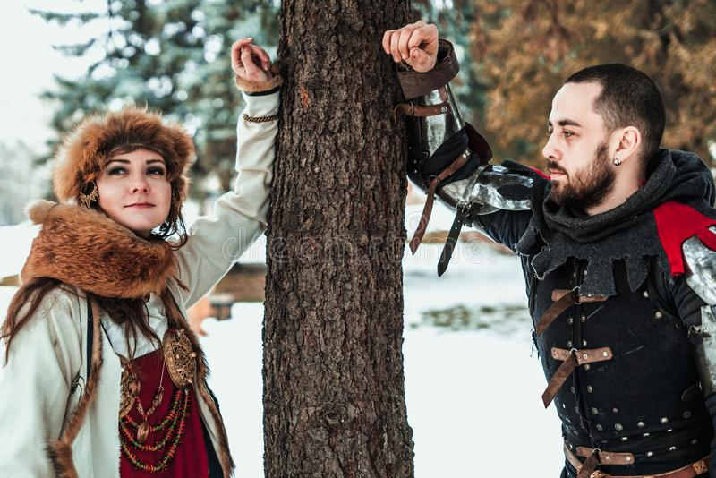 Man and woman in historical costumes near a tree royalty free stock photos