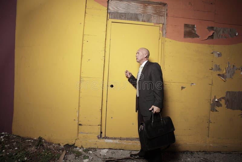 Man knocking on a yellow door. Businessman at night knocking on a yellow door royalty free stock photos