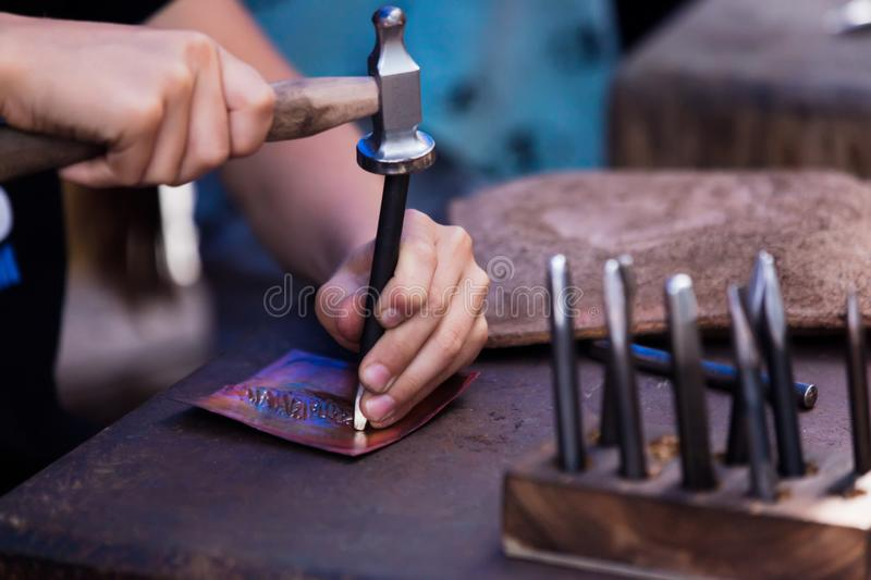 A man knocks on a chisel with a hammer during work.  royalty free stock photos