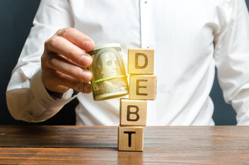 A man knocks down the tower with the word debt with the help of a bundle of money. Early repayment of the loan, remove interest. Charges and pay only the loan royalty free stock image