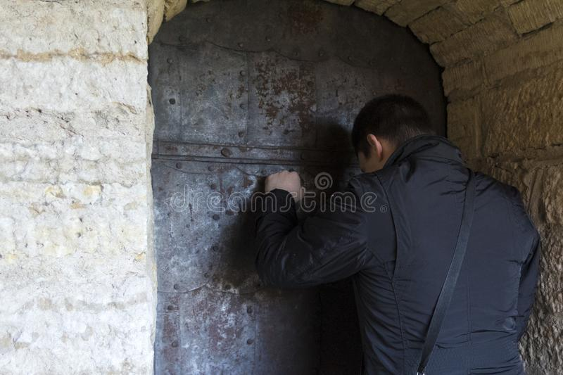 Man knocks. A man knocks on the iron door in the Old Fortress royalty free stock images