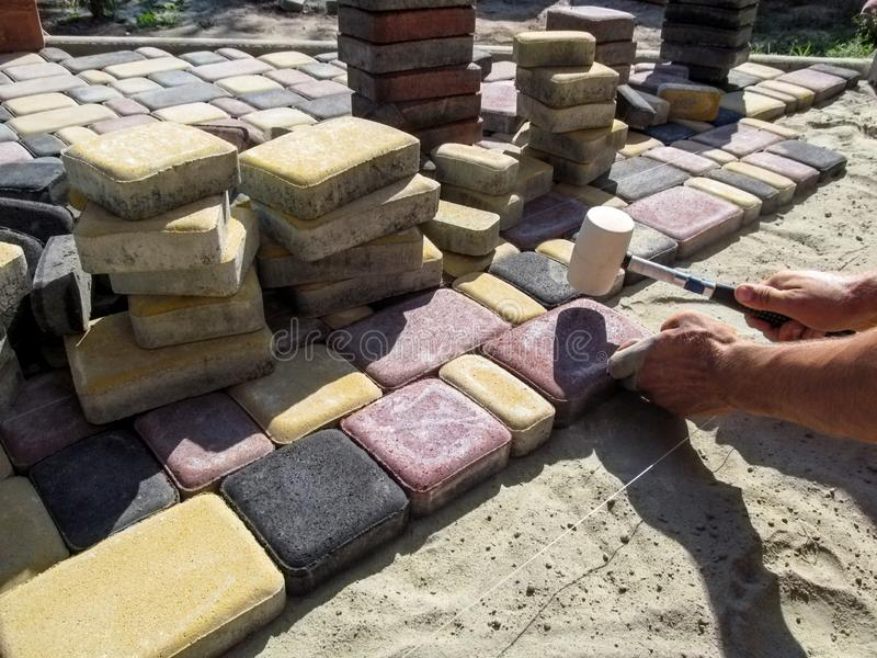 A man knocks on a multicolored sidewalk tile with a rubber mallet. Work on paving beautiful bright slabs on a patio or yard royalty free stock photography