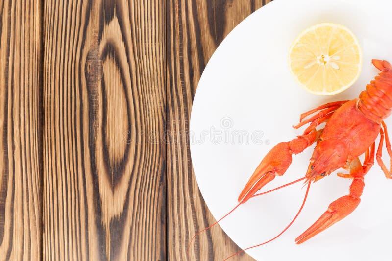 Man kokade den röda kräftan nära halva av citronen i den vita keramiska maträtten royaltyfria bilder