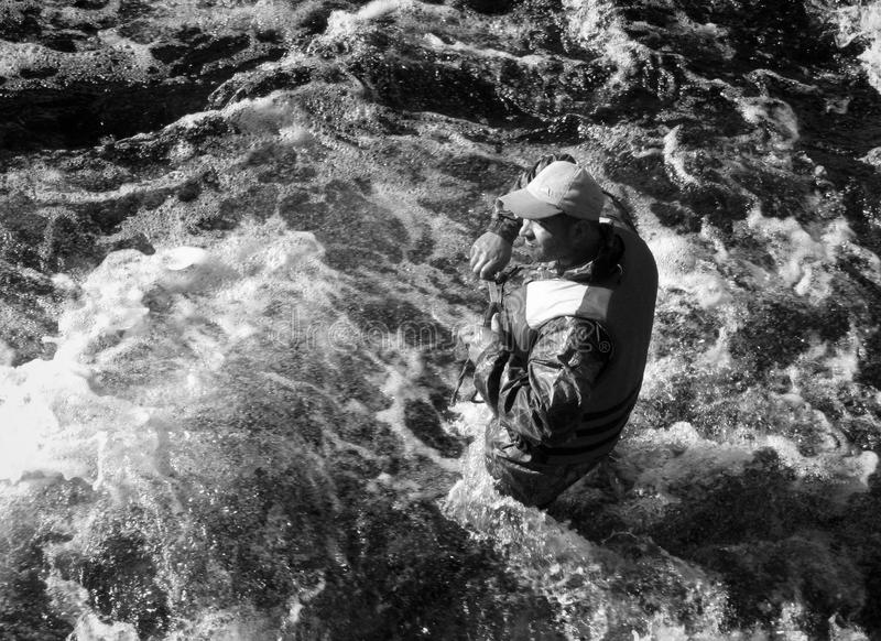 Man. KOLSKYY, RUSSIA - 11 AUGUST 2008: Man in the life vest standing in the water of the mountain river stock photos