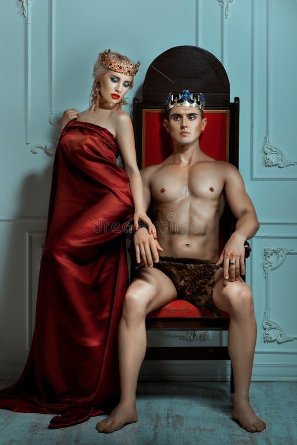 Man koningszitting op de troon naast Koninginvrouw stock foto's