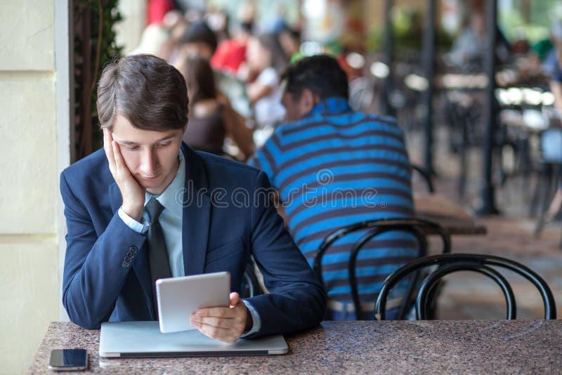Man kopplade av den unga stiliga yrkesmässiga affärsmannen som arbetar med hans bärbar dator, telefon och minnestavla i ett bullr arkivbild