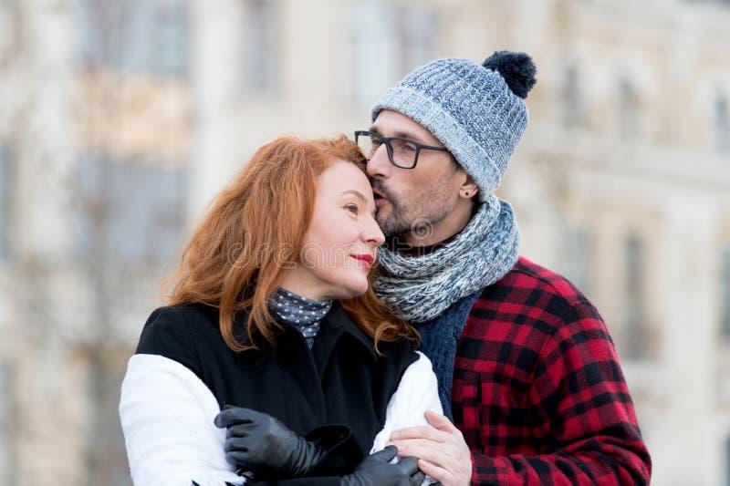 Man kussende vrouw in voorhoofd Man die in glazen vrouw kussen Kerel die meisje en kus omhelzen Familieliefdes buiten data stock afbeelding