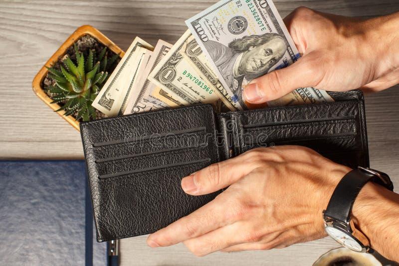 Man& x27; la s passa giudicare il portafoglio di cuoio nero pieno delle banconote in dollari fotografia stock
