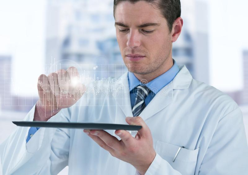 Man in lab coat with device and white graph with flare against blurry building stock photos