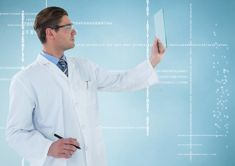Man in lab coat and goggles with pen holding up glass device against white interface and blue backgr stock photos