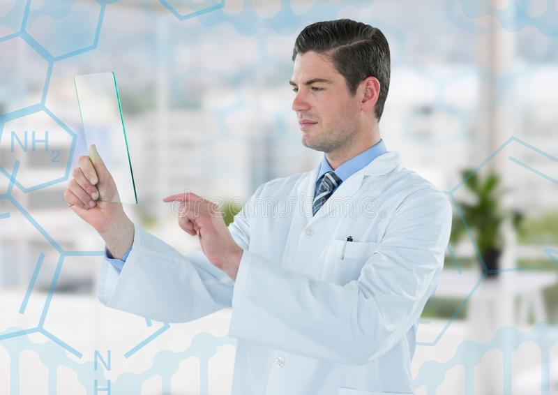 Man in lab coat holding up glass device against blue medical interface and blurry office stock photos