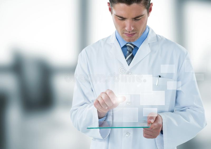 Man in lab coat looking down at glass device and square interface against blurry window royalty free stock images