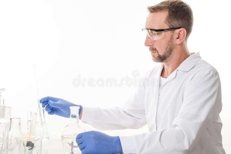 View of a man in the laboratory while performing experiments. Man in the laboratory, view of a man in the laboratory while performing experiments royalty free stock images