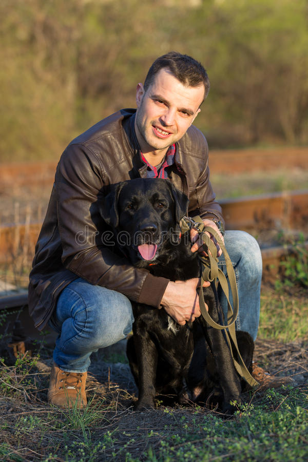 A man and a Labrador are sitting on the railroad in an embrace. royalty free stock photography