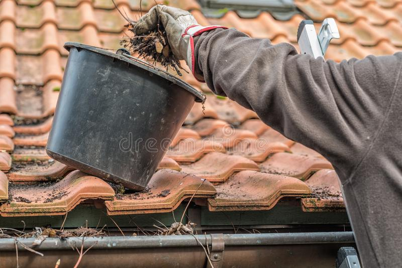 Man on a ladder cleaning house gutters royalty free stock images