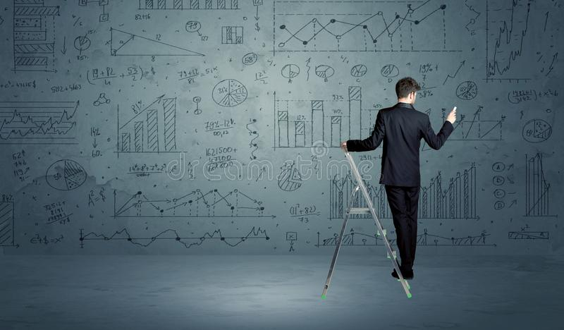 Man on ladder drawing charts. A businessman in modern stylish elegant suit standing on a small ladder and drawing pie and block charts on grey wall background stock images