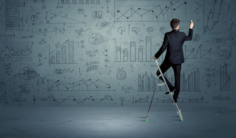 Man on ladder drawing charts. A businessman in modern stylish elegant suit standing on a small ladder and drawing pie and block charts on grey wall background stock photos