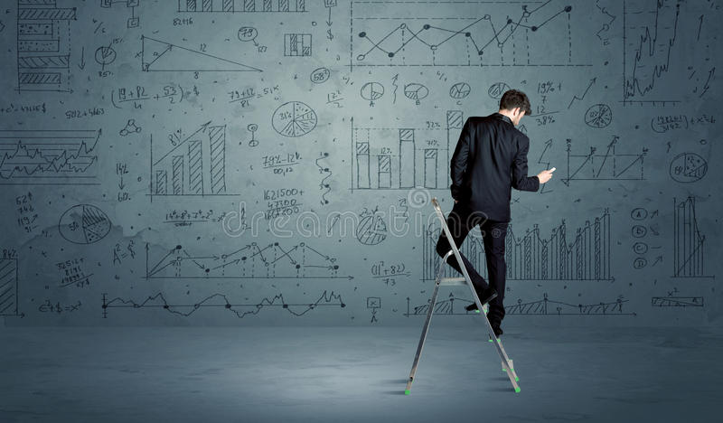 Man on ladder drawing charts. A businessman in modern stylish elegant suit standing on a small ladder and drawing pie and block charts on grey wall background royalty free stock photography